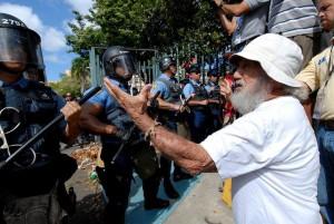 Manifestantes frente a la fuerza de choque