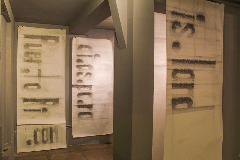 """Vista de la exposición con las piezas: Puerto Rican, 2017, 36"""" x 100""""; Diaspora, 2018, 36"""" x 81"""" y Island, 2018, 36"""" x 82"""", realizadas en grafito sobre papel por Lilliam Nieves."""