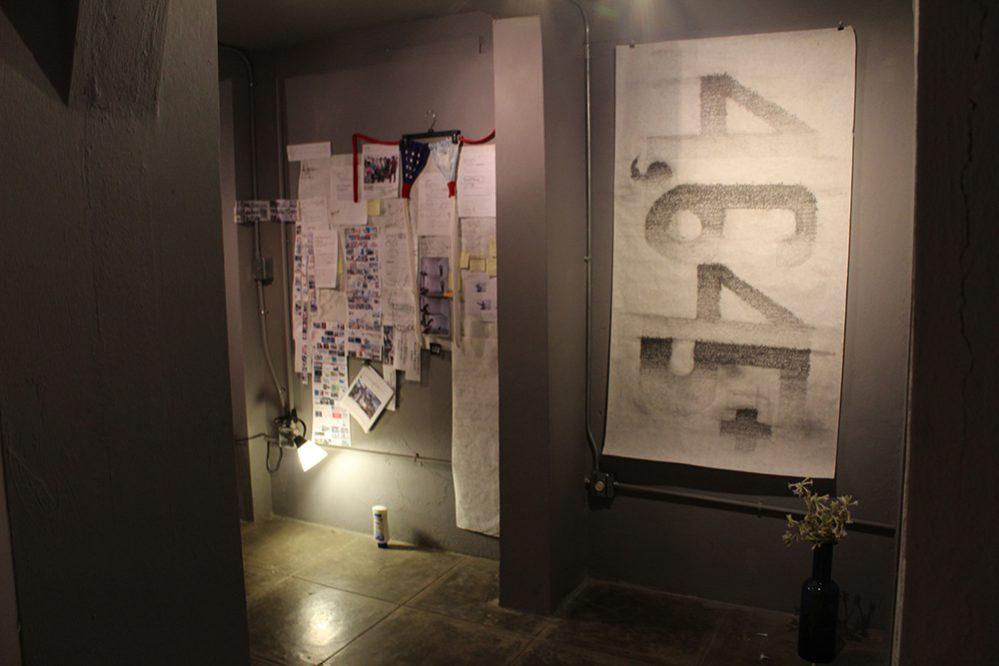 """Vista de sala con la instalación """"Script"""", 2017, papel, grafito, bolígrafo, plástico, retazos de papel, fotocopias a color y tela, 56"""" x 55"""" y """"Flags"""" (bikini), 2017, tela, plastico, metal, 14"""" x 41"""" de la artista Lilliam Nieves."""